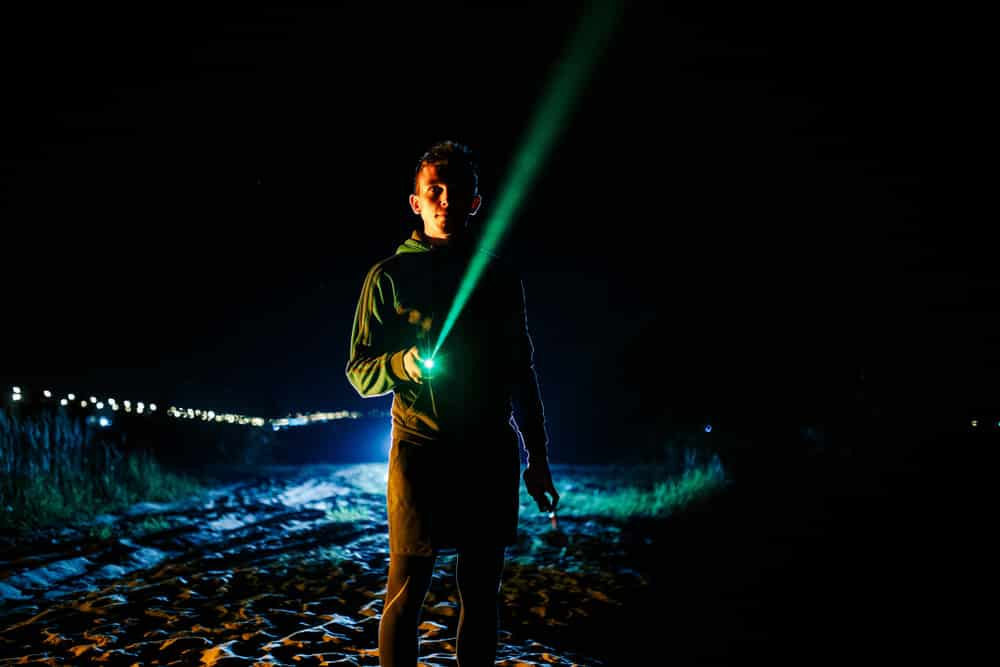 man pointing a green laser pointer toward the sky