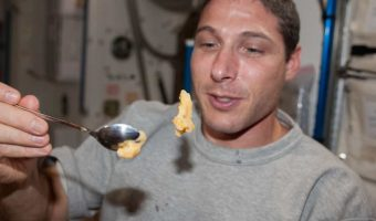 astronaut attempting to eat solid food