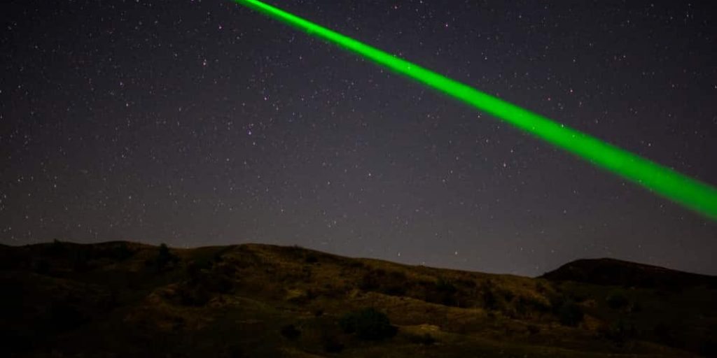 green astronomy laser pointer on starry sky