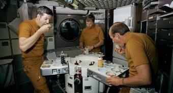 three astronauts enjoying their space meal